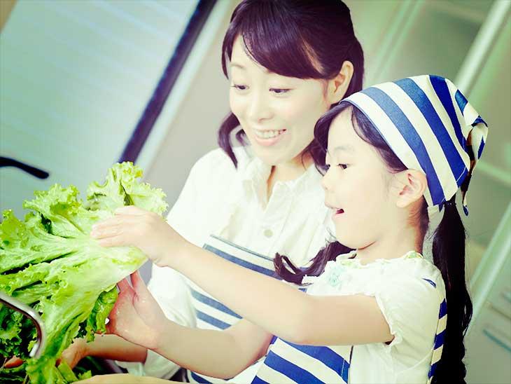 キッチンでママの料理の手伝いをシている女の子
