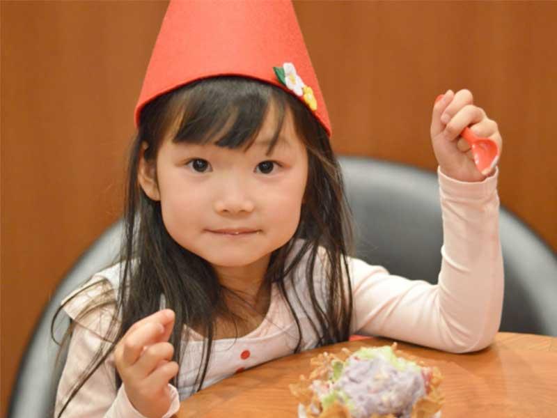 ケーキを食べながらハロウィンパーティーを楽しむ女の子