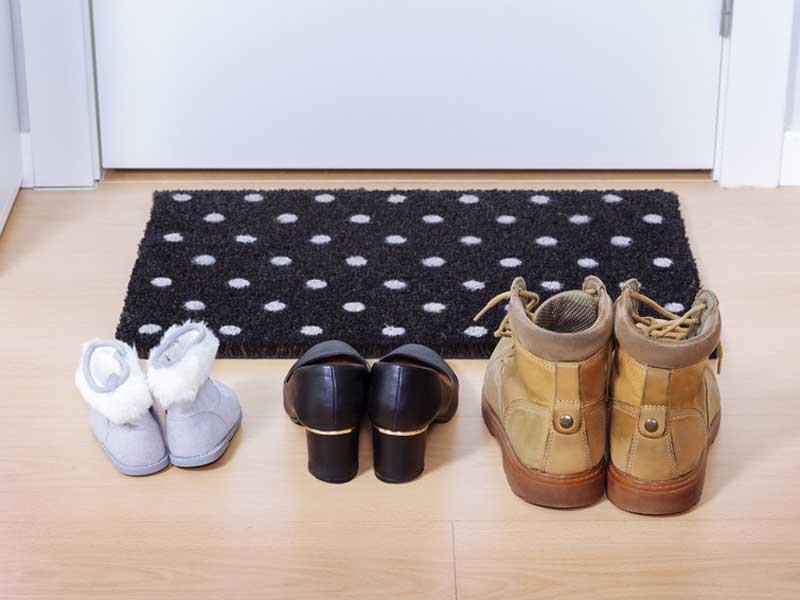 ドアマットの前に並ぶ靴