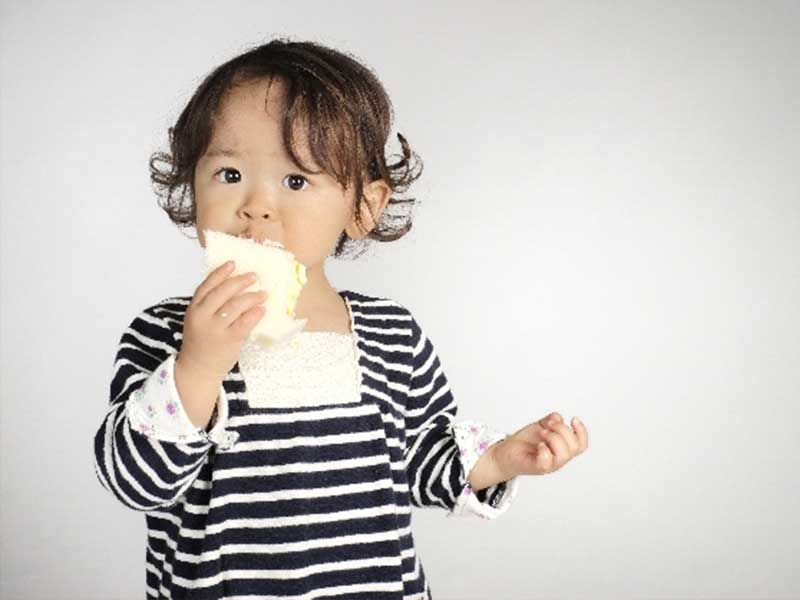 パンを食べる小さい女の子