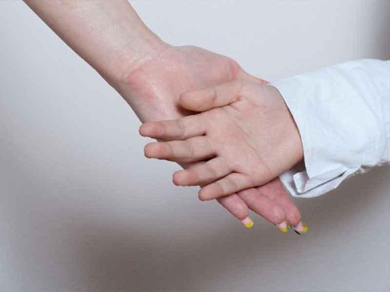 手のひらを重ねる母と娘