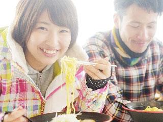 ラーメンを笑顔で食べる男性と女性