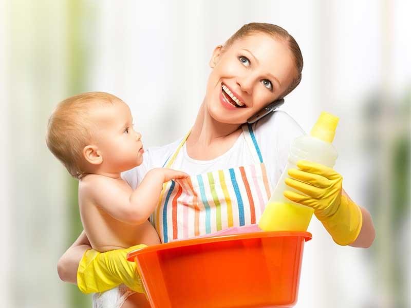 赤ちゃんを抱っこしながら家事をしているママ