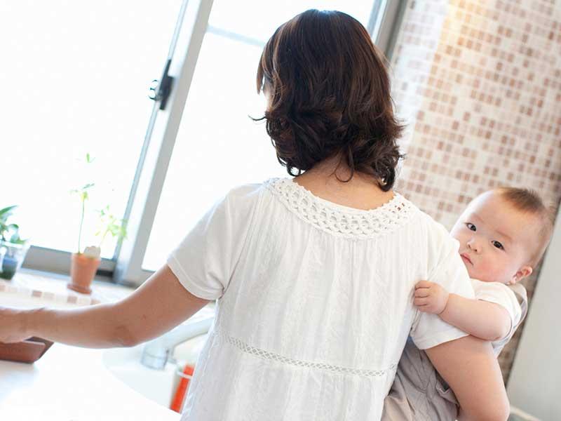 台所に立つ赤ちゃんを抱っこしているママ
