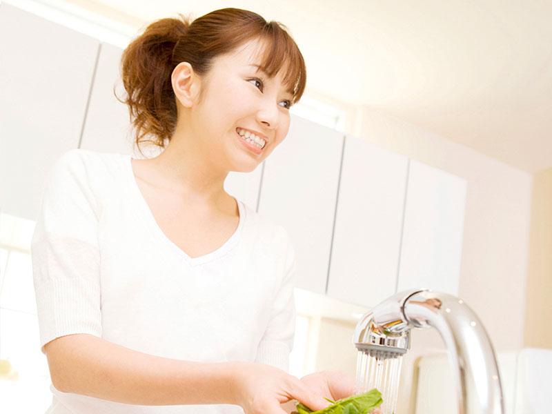 キッチンで野菜を洗っている主婦