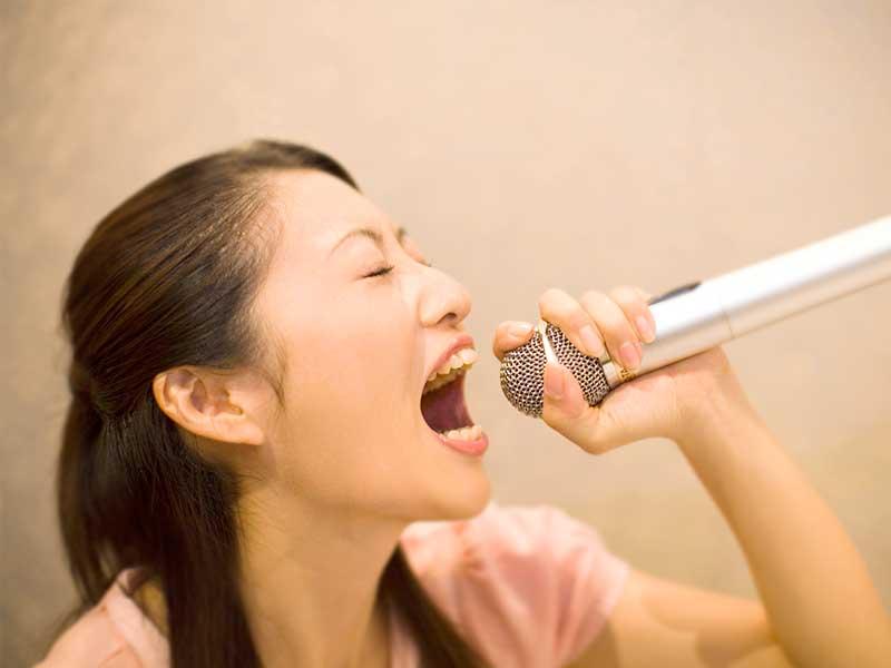 カラオケで歌う主婦
