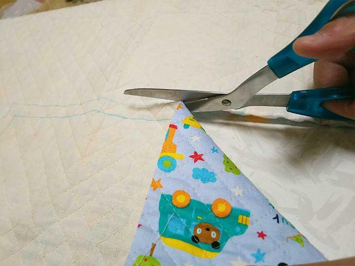 布をハサミで切っている