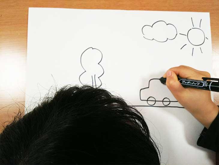 車の絵を描いている男の子