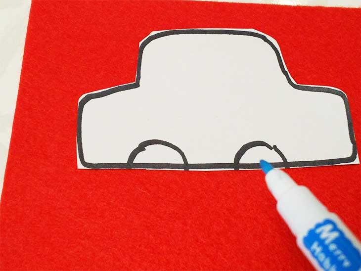 車の形に切り抜いた紙をフェルトにあててチャコペンでなぞっている