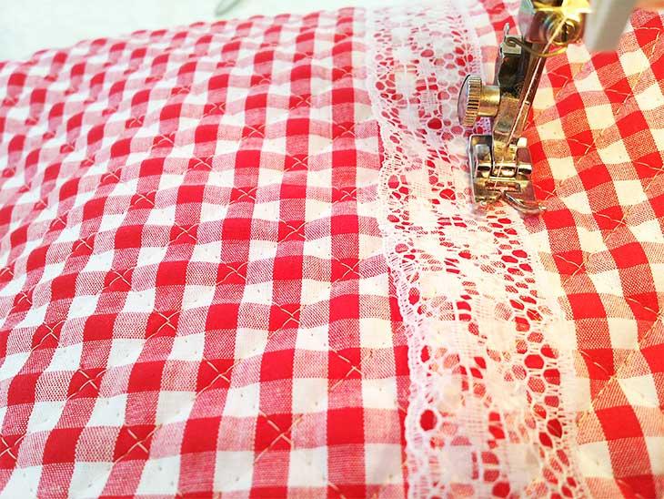 通園バッグの布にレースをミシンで縫い付けている