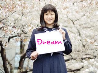 dreamという紙をもちながら笑顔で笑う中学生の娘