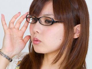 眼鏡に手をかけ考える女性