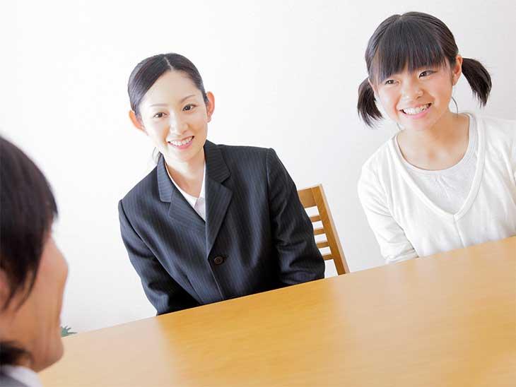小学校受験の面接で母親の隣に座って質問に答えている女の子