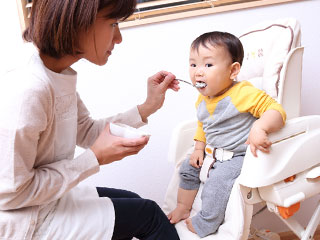 椅子に固定されて食べる赤ちゃん