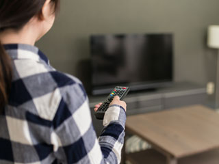 一人でテレビのスイッチを入れる女性
