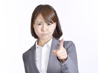 スーツ怒りながら指を指すスーツ姿の女性