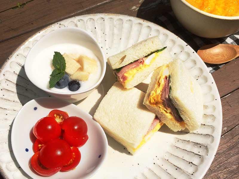 テーブルにサンドイッチとヨーグルトの朝食