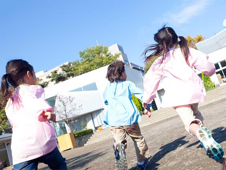 園庭を走っている幼稚園児