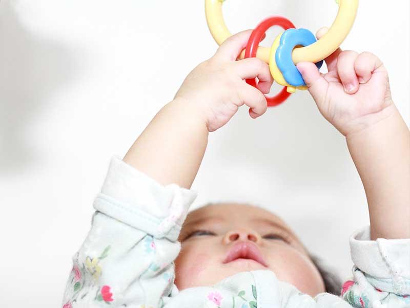 ぶら下がりおもちゃで遊ぶ赤ちゃん
