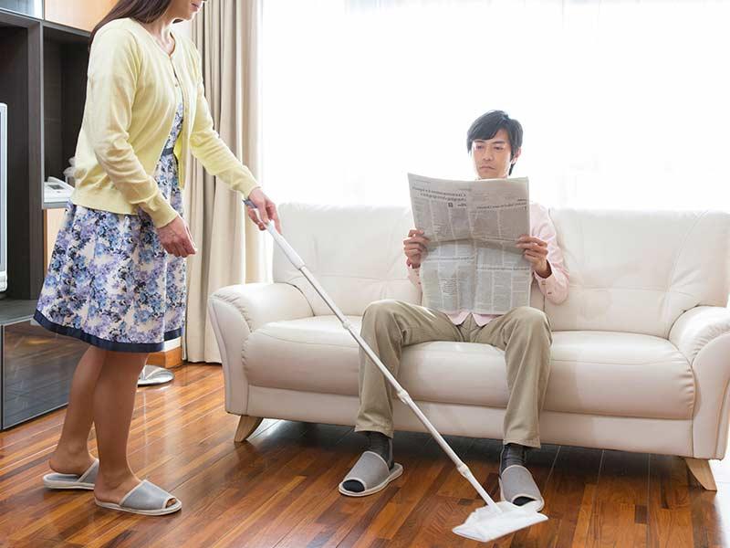 奥さんが掃除をする間に新聞を読む夫