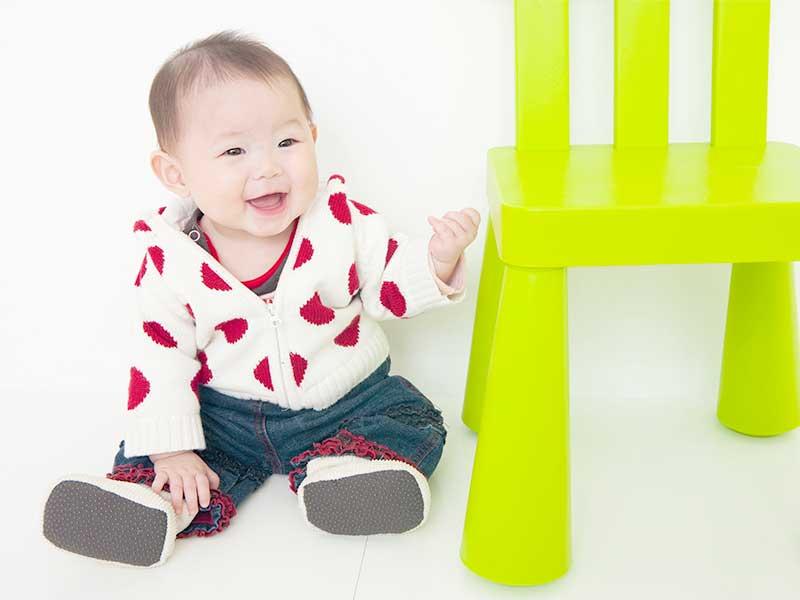 イスの横に座ってる笑顔の赤ちゃん