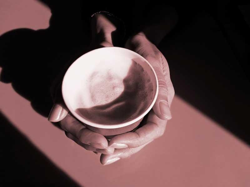 コーヒーを飲んでいる女の人の手