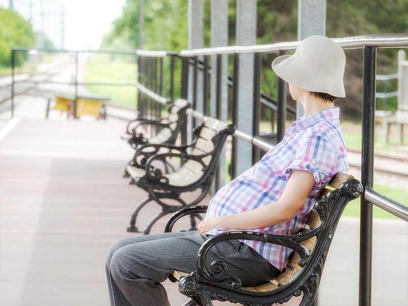 ベンチに一人で座る妊婦さん