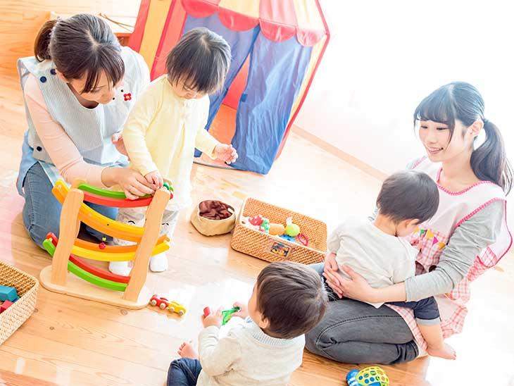 保育園の中で子供達と遊んでいる保育士さん