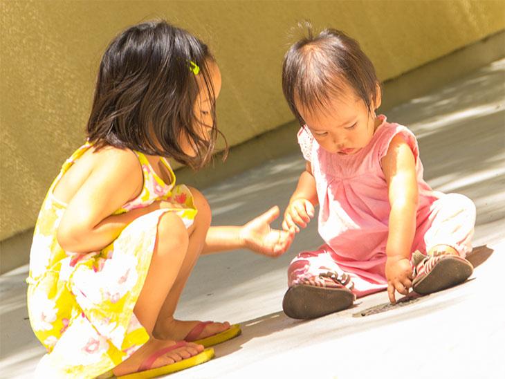 保育園の園庭で小さい赤ちゃんの面倒を見てあげている女の子