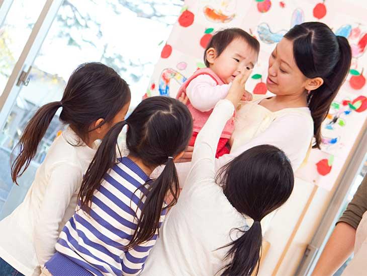 保育士さんが抱っこしている赤ちゃんを見上げている女の子達