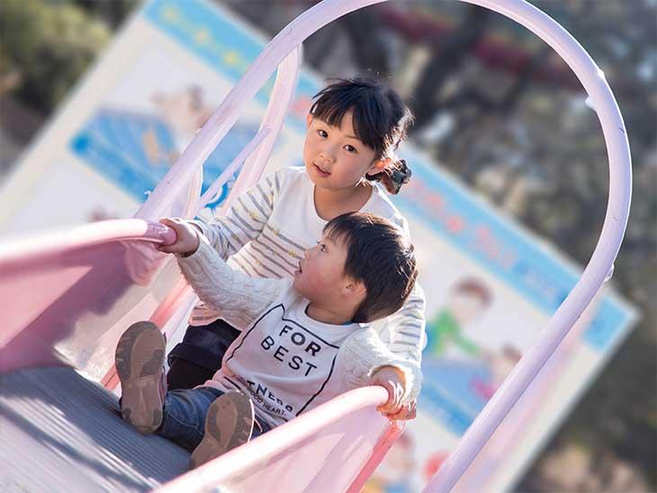 保育園の滑り台で小さい子を後ろから支えている女の子