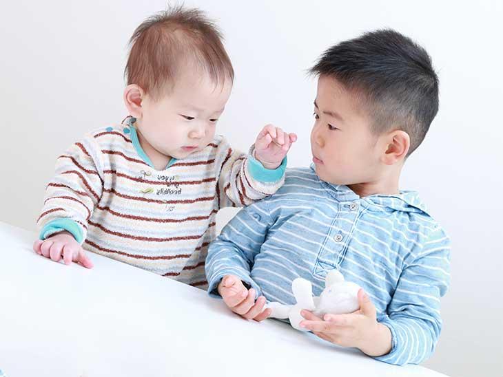 赤ちゃんを玩具であやしている男の子