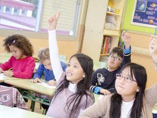 教室で手を上げる子供達