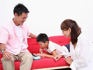 鍵盤ハーモニカを吹く子供と母親と父親