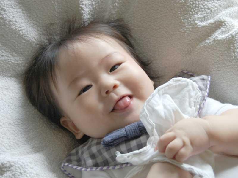 顔にかかった布を取る赤ちゃん