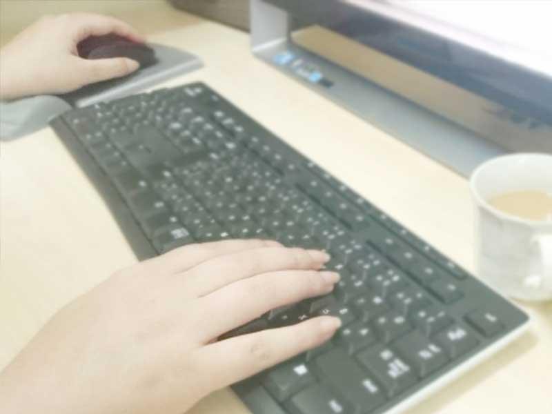 パソコンでネットサーフィンをする女性の手
