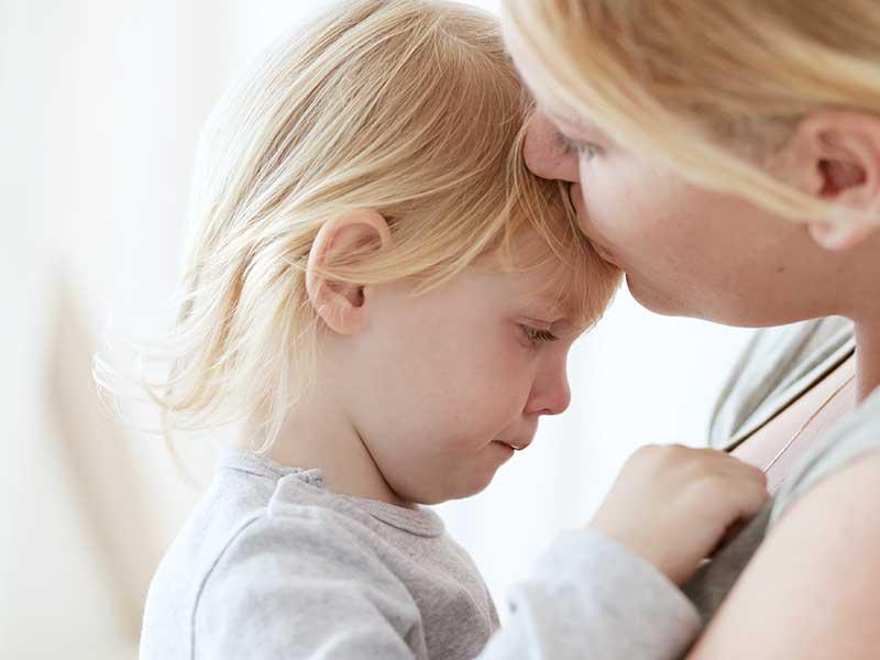 子供を抱っこしながら安心させるお母さん