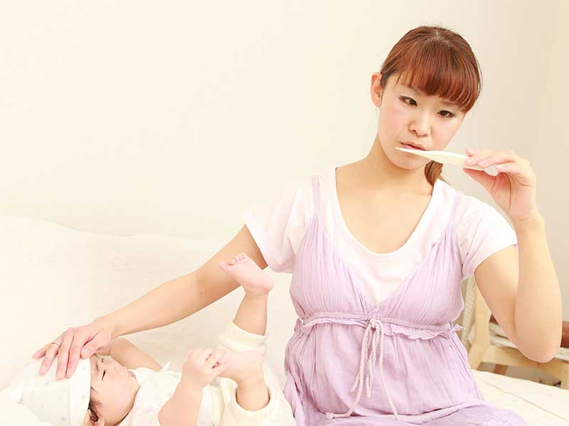 赤ちゃんの体温を計るお母さん