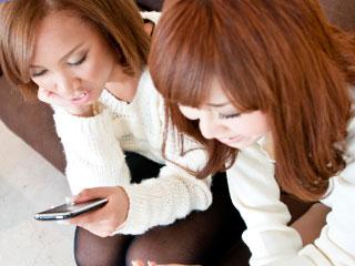 お互い携帯をいじりながら座って話す主婦