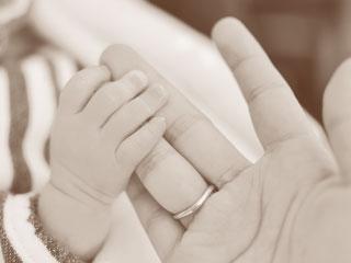 お母さんの手を握る赤ちゃんの手