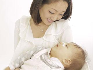 赤ちゃんを抱きながら微笑むお母さん