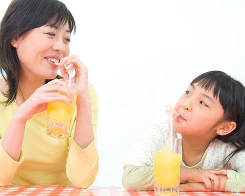 母親と娘がジュースを飲みながら会話する