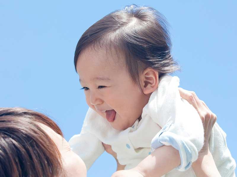 笑顔でママに抱っこしてもらう小さい子供