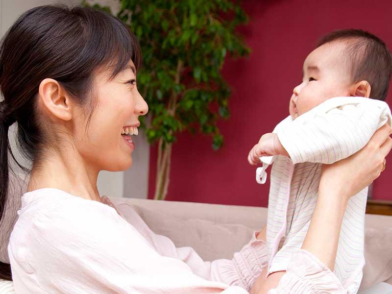 膝に乗せて赤ちゃんと遊ぶお母さん