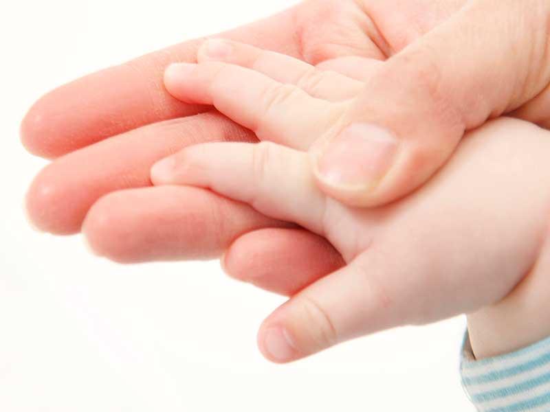 赤ちゃんの手を触るママ