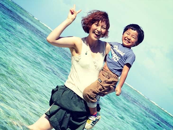 ママに抱っこされながら海で遊んでいる男の子