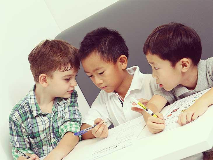 外国人の男の子たちに混じって一緒に勉強している日本人の男の子