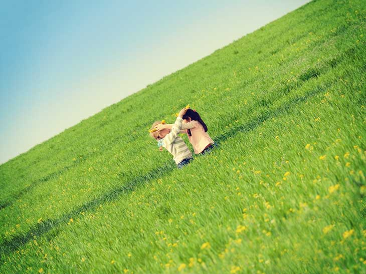 広い草原の中で花冠を掛け合っている外国人と日本人の女の子たち