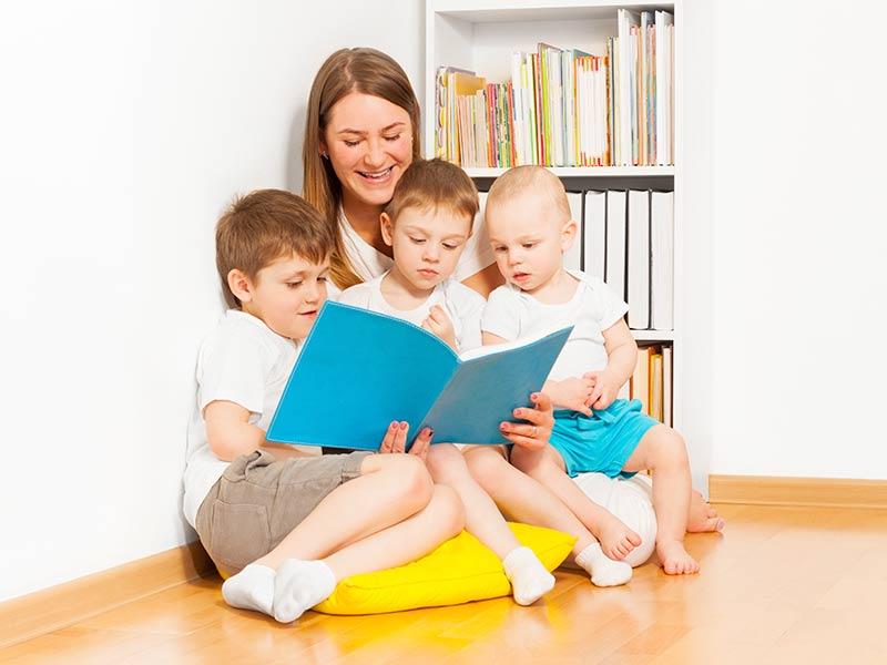 お母さんに本を読んでもらう子供達