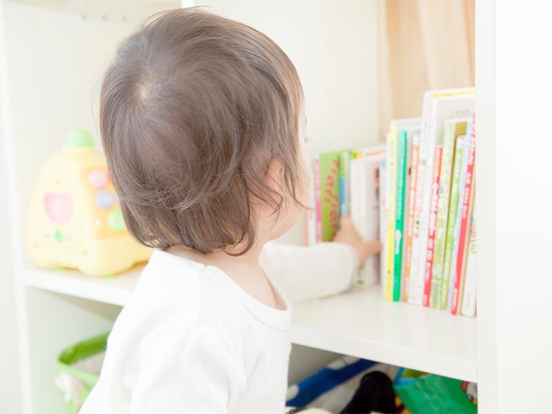 本棚の本をとる男の子